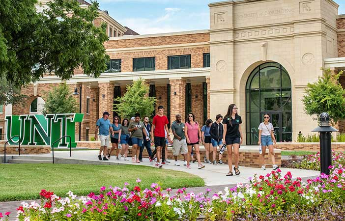 Students walk past the new UNT Welcome center photographed on Aug. 1, 2019.
