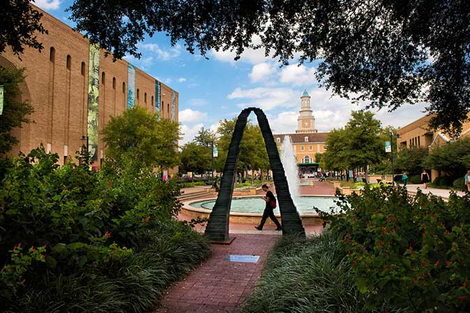 A student walks past the fount in the library mall on the UNT Campus.